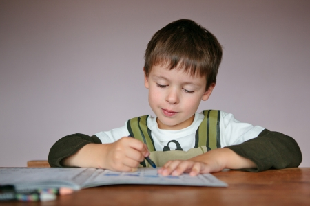 Young boy doing his homework at home, write something in his notepad