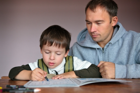 Father helping son doing homework  Parent with child writing  photo