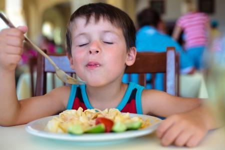 Schattige kleine jongen genieten van voedsel Kind eet pasta met groenten Stockfoto