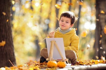 canva: Cute little boy painting with brush outdoors in park on beautiful autumn day