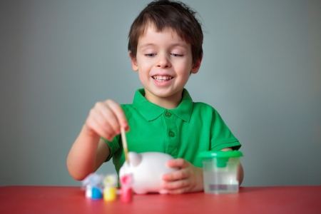 boys only: Cute happy little boy painting his piggy toy Stock Photo
