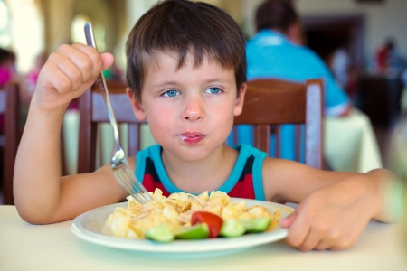 junky: Cute little boy enjoying food  Child eating pasta with vegetables Stock Photo