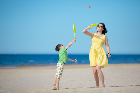 Young loving mother and her little son playing on the beach photo