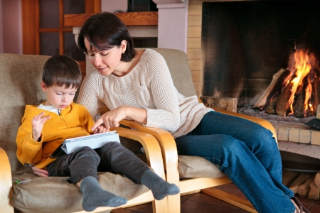 Mother and son playing on digital tablet PC  in front of fireplace
