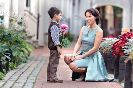offering: Little boy giving flower to his mom on mother s day Stock Photo