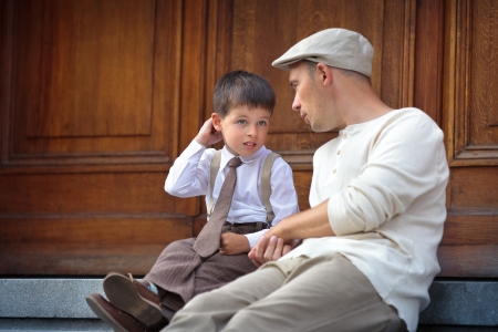 dos personas conversando: Feliz padre e hijo hablando y que tiene al aire libre en el resto de la ciudad en ciudad en d�a de verano hermoso