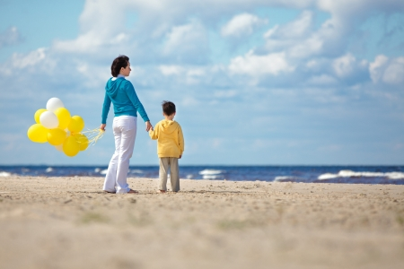 Mother and little son with yellow balloons on the beach on beautiful summer day photo