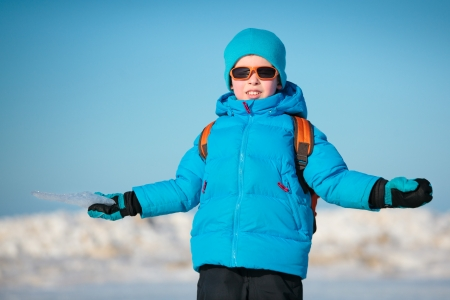 Portrait of cute little boy outdoors standing on winter beach on cold winter day photo