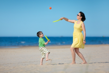 Young loving mother and her little son playing on the beach Stock Photo - 17640146