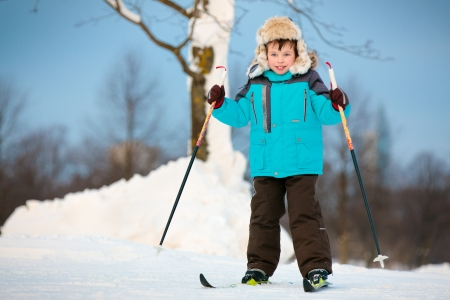 Happy little boy skiing on cross