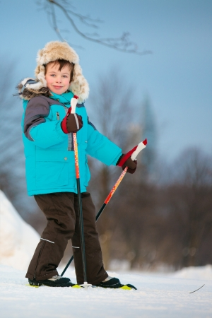 Portrait of cute little boy skiing on cross photo