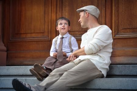 padres hablando con hijos: Feliz padre e hijo hablando y que tiene al aire libre de descanso en la ciudad en d�a de verano hermoso