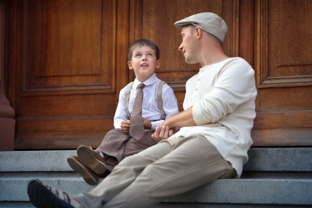 Happy father and son talking and having rest outdoors in city on beautiful summer day
