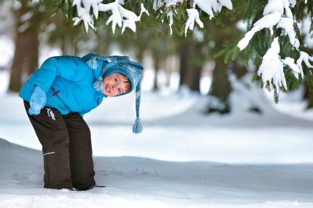 outwear: Cute five years old boy playing on winter forest