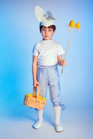 bunny ears: Lindo chico con orejas de conejo y llevando una cesta de Pascua Foto de archivo