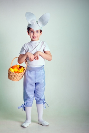 A happy little boy holding his easter basket and wearing bunny ears  He is on the hunt for more eggs   photo