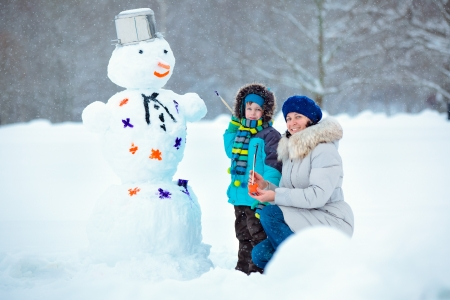 Cute little boy with his young mother painting a snowman