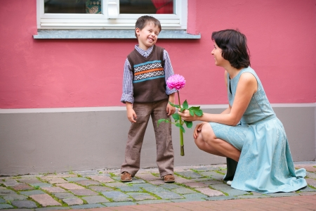 Happy little boy talking with his mother outdoors in city Фото со стока