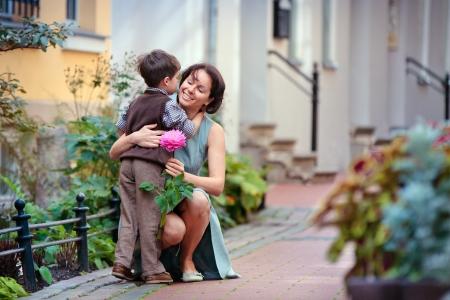 mamans: Petit gar�on donnant la fleur � sa maman le jour de m�re s Banque d'images