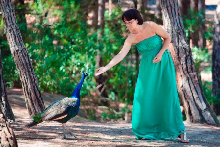 Young attractive woman feeding peacock in forest