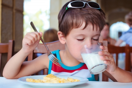 Cute little boy having delicious breakfast in outdoor cafe