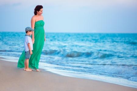 maxi dress: Mother and her little son enjoying beach Stock Photo