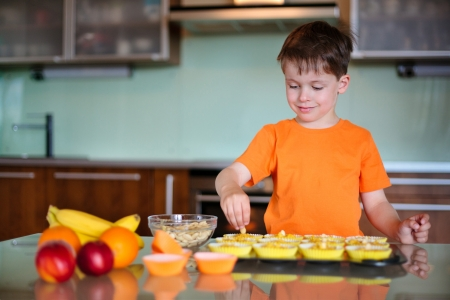 Cute little boy helping with baking cookies in the kitchen photo