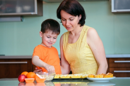 Young mother and her little son baking muffins in the kitchen photo