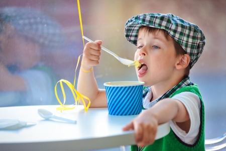 Cute little boy eating ice cream at indoor cafe 版權商用圖片