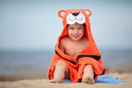 Cute little boy wearing tiger towel sitting at the beach Imagens