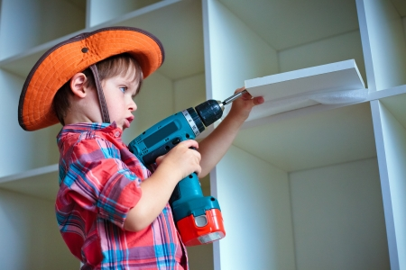 Cute little boy using an electric screwdriver Stock Photo