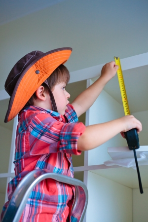 poker faced: Cute little boy measuring a part of cupboard