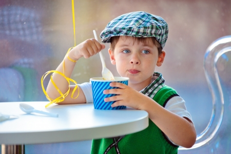 Cute little boy eating ice cream at indoor cafe photo