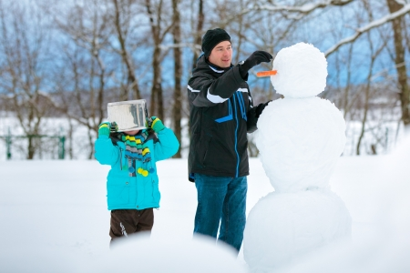 Little boy with his father making a snowman and having fun photo