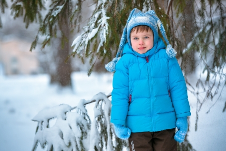 Cute little boy playing outdoors in a winter forest Stock Photo