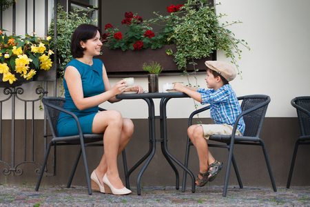 Mother and son sitting in outdoor cafe