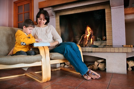 Mother and son playing on digital tablet PC in front of fireplace 版權商用圖片