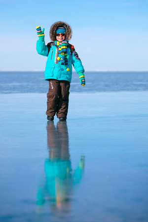 Cute little boy outdoors standing on frozen sea Imagens