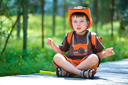 Portrait of a cute little boy in summer forest