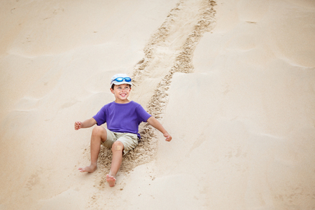 Cute little boy rolled down the slope of snow-white dunes at Tarifa, Andalusia in Spain