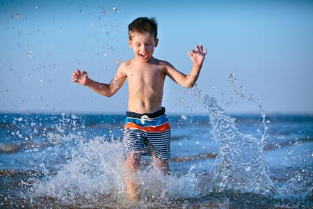Cute little boy running through the water at the beach Фото со стока