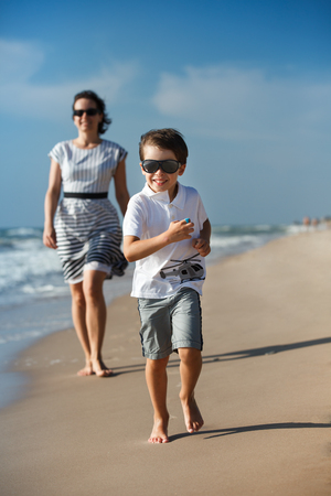 Mother and her little son playing on the beach Фото со стока