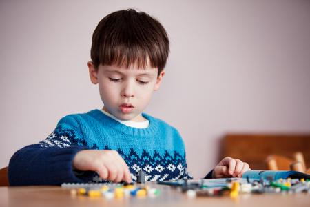 Niño de 5 años jugando con bloques de construcción.