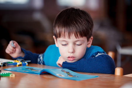 Concentrated child reading a manual before do-it-yourself project