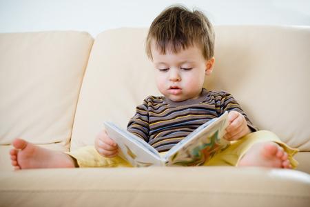 Cute little boy reading book on sofa