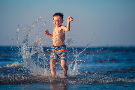 Cute little boy running through the water at the beach 스톡 콘텐츠