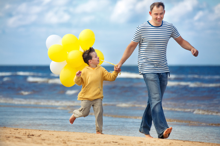 Father and little son with yellow balloons playing on the beach on beautiful summer day