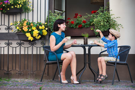 Young mom having coffee with her son in street cafe Foto de archivo