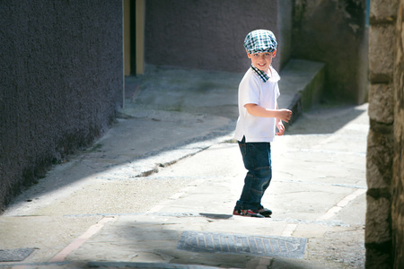 Cute little boy crossing narrow street