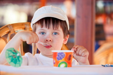 Cute little boy eating ice cream at indoor cafe on beautiful summer day